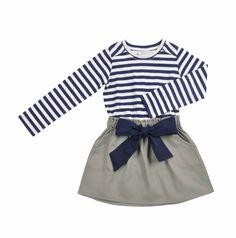 Vestido para niña. La parte de arriba con mangas largas en tela a rayas en azul marino y hueso. La falda es de color verde olivo y con bolsillos a los lados y una cinta en color azul marino que se enlaza al frente.