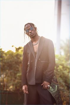 Travis Scott rocks a double-breasted jacket, tank, and shorts by Givenchy with RetroSuperFuture sunglasses.