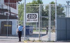 a group of baseball players standing next to a fence: A guard stands outside the gates of the immigrant holding centre in Laval, Que.