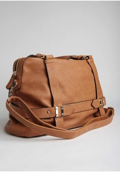 <p>Crafted in soft, tumbled faux leather, this cognac-brown purse features gold-toned hardware and a strap detail around the bottom. Complete with a rounded top with a zipper closure, an optional shoulder stra,p and black and white striped lining.