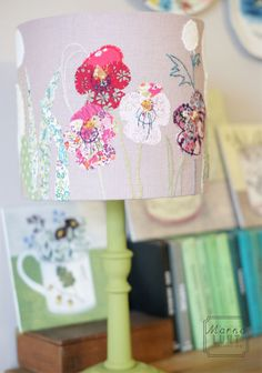 A hand embroidered lampshade of Pansies and Dandelions on a painted stand available on www.marnalunt.co.uk