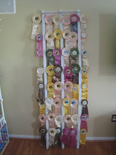 Cute way to display all of those old horse show ribbons...painted an old trellis white and put them on it.