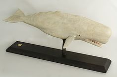 """Full-bodied carved and painted white sperm whale by Frank Finney.   8 ½"""" x 19 ½""""  For more information please email us or call 508-228-9623."""