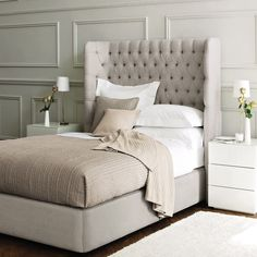 dramatic tufted headboard, contemporary side tables and wood trim. restful.