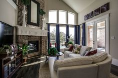 Great brick fireplace with White mantle. Although not a large space the windows and french doors give a sense of space. Sectional sofa is a perfect fit for the angles in the room.