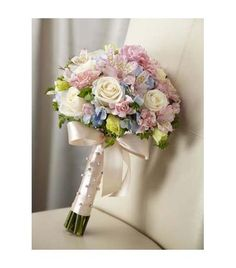 he FTD® Sweet Innocence™ Bouquet blooms with sweet sentiments and endearing charm to get you to look your bridal best on your wedding day. Gorgeous cream roses, pink mini carnations, pink Peruvian Lilies, pink double lisianthus, blue hydrangea and bupleurum are brought together to create an unforgettable bouquet. Tied together with a soft peach satin ribbon accented with pixie