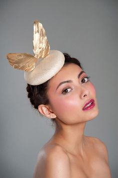 Golden Wings | Awon Golding Millinery | Spring/Summer 2013, Racing Collection | Hand-shaped gold lacquered goose feather wings on a pinokpok base. It fastens to the head with elastic which fits snugly at the back of the head, and is hidden by the hair to give an invisible effect | Hand-made in London