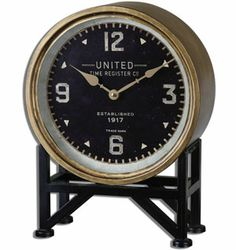 The Uttermost 06094 Shyam Table Clock is a high-quality, modern table clock designed by Steve Kowalski. Its elegant metal frame features a brass finish and rests in an aged black stand. New to Klockit.com!