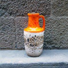 Este atractivo jarrón es altamente apreciado por coleccionistas. Se trata de atractivo jarrón con esmaltemarrón, beige y naranja de de lava 'crujido' texturizado. Se encuentra en excelentes condiciones vintage En su base se aprecia el sello 404-26 W. Germany. Medidas: H26 cm x Ø13 cm approx Recogida en tienda (Barcelona) y también envío.