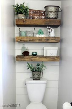 Farmhouse bathroom with wood floating shelves above toilet with shiplap accent wall #bathrooms #shelves #home #decor #designs #ideas