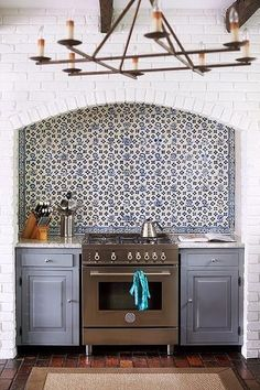 moroccan tile backsplash; blue kitchen cabinets, brick niche