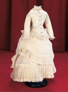 Of sheer finely-woven white muslin,the two-piece gown comprises a dart-fitted jacket with silk buttons,coat sleeves,lace collar,and a lower border of lace-edged pleats that match the border on the flounced over-skirt and on the skirt. The pleats are cleverly designed so they become longer from jacket to over-skirt and from over-skirt to lower hem. French,circa 1875.