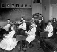 Escuela de Potomac en Washington, 1910. Shorpy. Una clase en la escuela de Potomac, Washington. En la pizarra, escrita con la cuidada letra del profesor, una cita de Kipling preside el aula. Las sillas y las mesas están atornilladas al suelo.