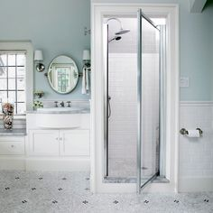 Blue and white tiles provide a serene color palette for the shower and complement the colors in the rest of the bathroom. Traditional white moldings and silver accents add elegance