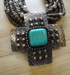 #22965 Cheyenne Necklace  Cheyenne Necklace    Brown and silver beads with copper and turquoise cross pendant.            Price:$75.95
