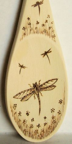 Dragonfly, flowers on a wooden spoon
