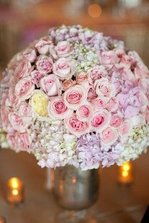 I like the use of hydrangeas and roses together and the sheer pastel colors. Would prefer a less formal, airy arrangement with greens