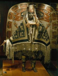 This Nisga'a chief is shown in his role as Great Dancer. Behind him is a ceremonial screen depicting a supernatural ancestor.