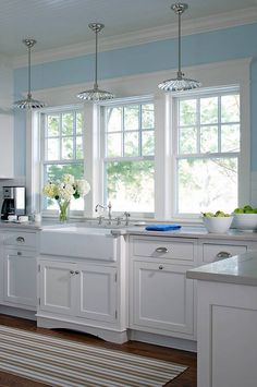 Kitchen with blue walls, white cupboards and Hudson Valley Heirloom Pendants.