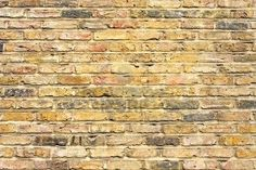 Pale beige and grey brick wall-ours will have less yellow