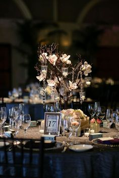 A manzanita branch centerpiece with orchids and hanging candles.