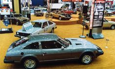 "1980 Chicago Auto Show. Datsun's 280-ZX sports car is in the foreground of this scene at the Japanese automaker's exhibit space, on the main floor of McCormick Place. Three versions were available: base hatchback, GL, and GL 2+2. Other Datsun models are visible toward the rear of this long, wide shot, including a 310 model whose doors reads ""Shadow Traffic.."" A vertical sign promotes the restyled 200-SX sport coupe."