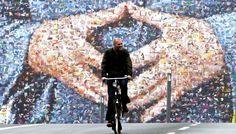 Un cycliste passe devant une affiche représentant les mains de lachancelièreAngela Merkel à Berlin, le 3 septembre.