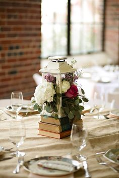 Floral centerpieces in lanterns. Antique book centerpieces. Flowers, wedding planning and styling by Regalo Design.