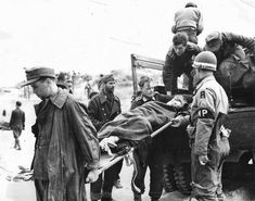 German prisoners unload a wounded comrade.