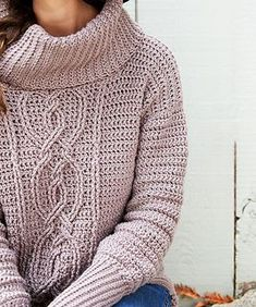This cowl-neck sweater features loads of texture and a flattering high-low hemline. The gorgeous entwined cable is crocheted with an interesting combination of stitches.