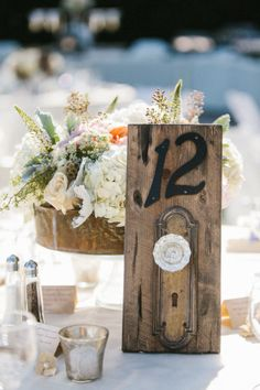 Table numbers - attach vintage keys to the escort cards... also love the flowers on a pedestal behind the table number.