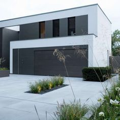 Modern front garden with raised bed, goat grasses and individual lighting Modern Driveway, Driveway Design, Exterior Design, Interior And Exterior, Contemporary Garage Doors, Concrete Driveways, Facade House, Modern House Design, Future House