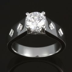 Flush set princess diamond accents with prong set 1.00 carat brilliant cut center. Gorgeous princess diamond detailing beautifully highlight the feature diamond.  Try on this design in our showroom.
