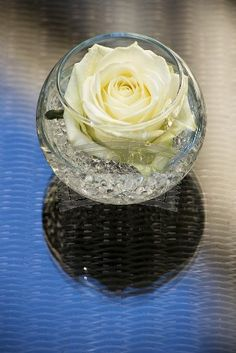 Centerpiece idea - single white roses sitting in small round glasses surround bigger centerpiece