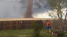 Stunning photo shows a man casually mowing his lawn as tornado looms >>> He said he was keeping an eye on it.  The twister, unusual for that part of Alberta, Canada, was moving at about 50 mph.