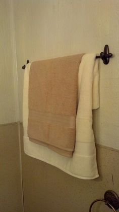 Towel bar made with 2 command hooks and a curtain rod