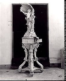 Phonograph cabinet built with Edison cement, 1912. The clockwork portion of the phonograph is concealed in the base beneath the statue; the amplifying horn is the shell in behind the human figure.