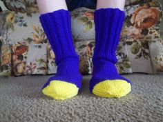 Here is a wonderful pair of hand knit adult size socks. Heel to toe is approx. 9 1/2 in. and the ribbing on the top (top to ankle) is approx. 6 1/2 in. The yarn colors that were used were Amethyst for the base color and Bright Yellow for the heels and toes.  These socks are made of 100% acrylic yarn and can be machine washed and dried.