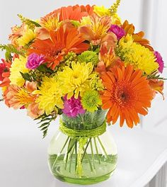 Birthday Flowers - FTD Because You're Special Bouquet - Perfect for a birthday, special day, or just any day.  Tell someone how special they are to you. Send this exuberant, brightly colored bouquet of orange Gerbera daisies, yellow poms, hot pink mini carnations, and vivid green button poms in a sleek, beaded green glass vase. Guaranteed to bring a smile! Approx. 11H x 10W