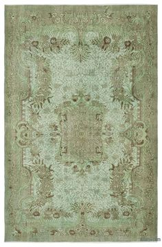 """For a contemporary look with abstract appeal, this green over-dyed rug is skillfully crafted by the revitalization of a hand knotted vintage Turkish rug. Made from wool on cotton, this """"distressed"""" rug measures 191 cm x 288 cm. The process in creating these works of art begins by shearing to lower the pile and to help """"distress"""" them. They then undergo a series of processes to remove the color. They are now ready to be dyed in one color, a stage that can be repeated several times to reach t…"""