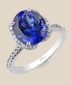 An azure tanzanite sits upon a pedestal of diamonds set in 18K gold. Diamond Info: 54-RD 0.43, 01-TNZ(H) 4.40 CTS Fits center stone size OV: 11x9 MMGUIDE Price may vary depending on center stone.