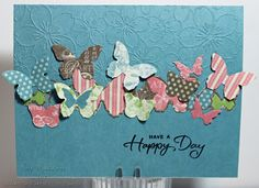 Butterfly die cuts fluttering over over a Darice  Cherry Blossom embossing folder card design.