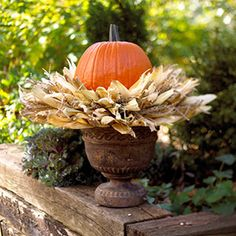 Hot glue corn husks to a straw wreath form,along the top, bottoms and sides so that the ends of the husks all point outward. Stick sprigs of ornamental grass into the wreath form to fill in any gaps. Set the wreath on top of a garden urn and nestle a pumpkin