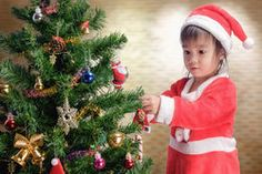 Merry Christmas.Cute little child is decorating the Christmas tree.