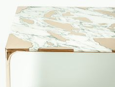 Large slabs of marble were cut with a water jet to reveal the inner bronze surface of this table.