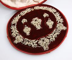 Lot# 1035 An antique seed pearl demi-parure.Circa 1825, of multiple seed pearls strung and loosely sewn onto a mother-of-pearl frame including; a pair of earrings with detachable drops, a brooch and a necklace, 16'', with a fitted leather case embossed 'C. Gray, March, Cambridgeshire, 1827', 4 pcs, , est: $300/500 *Price Realized: $2,400.00