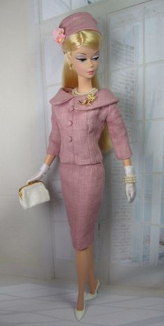 This vintage style two piece suit is cut form antique rose pure linen, fully lined, and features a fitted jacket with three-quarter length sleeves, collar and center seam accented by covered buttons. Button over snaps closes the back. The matching pencil skirt is fully lined with button over snap back closure. The bias cut  hat is fully lined and finished with vintage style milliners forget me nots. A set of jewels includes a double strand necklace of cream faux pearls, a pair of earrings…
