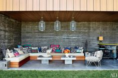 Punchy hues accent Muriel Brandolini's Hamptons home, which was featured in the August 2014 issue of Architectural Digest. An outdoor seating area is furnished with a custom-made teak sofa and concrete tables by CB2; the brightly colored accent pillows are made of fabrics from the designer's line for Holland & Sherry, and the lanterns are by Pols Potten.