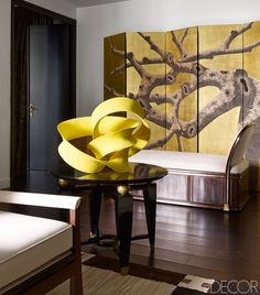 A corner of fashion designer Andrew Gn's sleek Paris living room features a bold sculpture by Merete Rasmussen and an elegant folding screen.