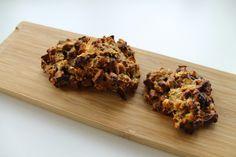 """Start med at riste mandlerne i ovnen i 5-8 minutter ved 180 grader. Lad dem afkøle lidt, hak dem groft, kom dem i en skål sammen med salt, havregryn og æg og rør det godt sammen. Rør også peanutbutter i. Smelt kokosolien (fx i mikrobølgeovn), hak dadler fint og chokolade groft og kom alle 3 ingredienser ned i skålen. Rør det godt sammen. Fordel 6-7 """"klatter"""" på en bageplade med bagepapir og tryk dem lidt flade. Bag dem i cirka 10 minutter ved 190 grader."""